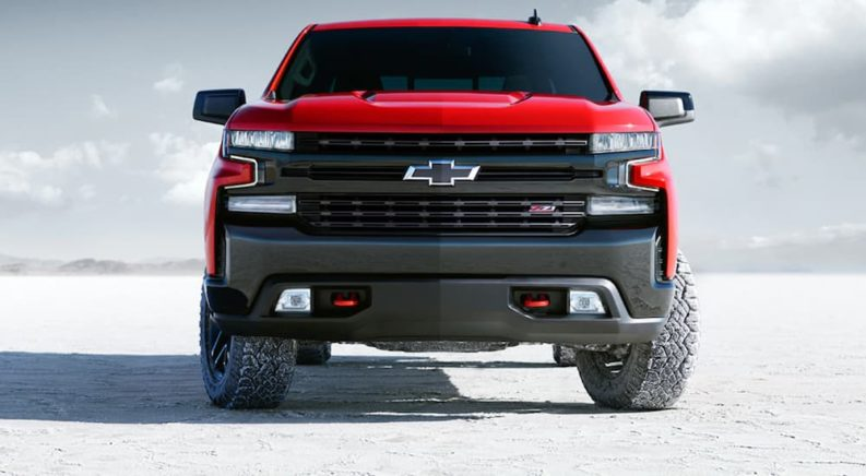 A red lifted Chevy Silverado 1500 is parked on snow.