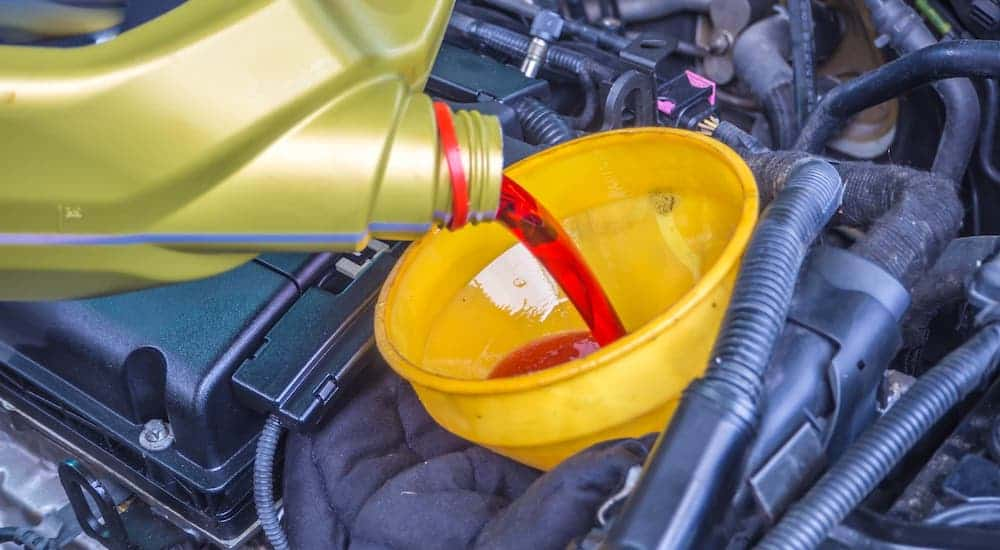 Transmission fluid is being poured into a car, a part of routine Transmission Service.