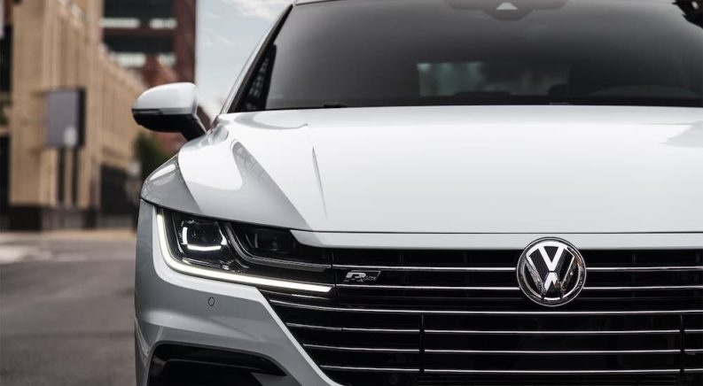 A closeup is shown of the grille and front of a white 2020 Volkswagen Arteon.