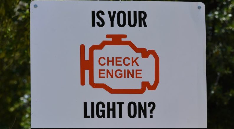 A white sign shows the check engine light symbol and the text 'Is Your Check Engine Light On?'