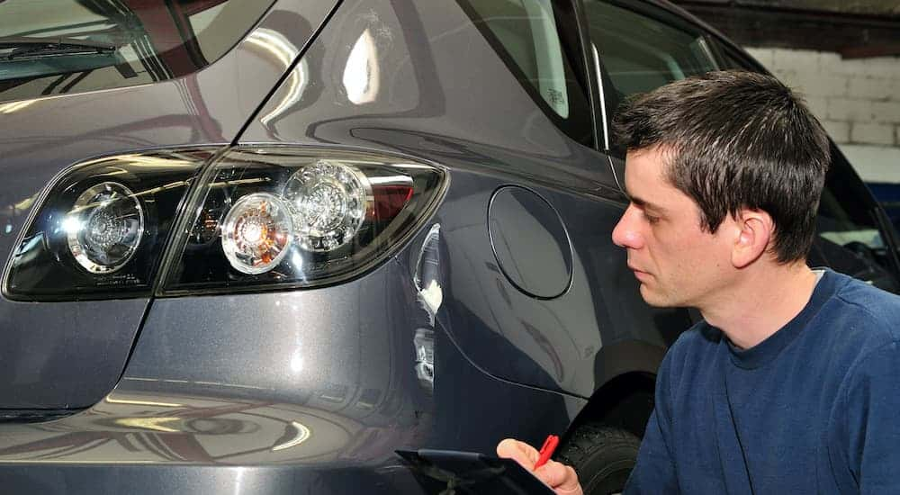 A person is shown inspecting rear fender damage at an autobody repair shop near you.