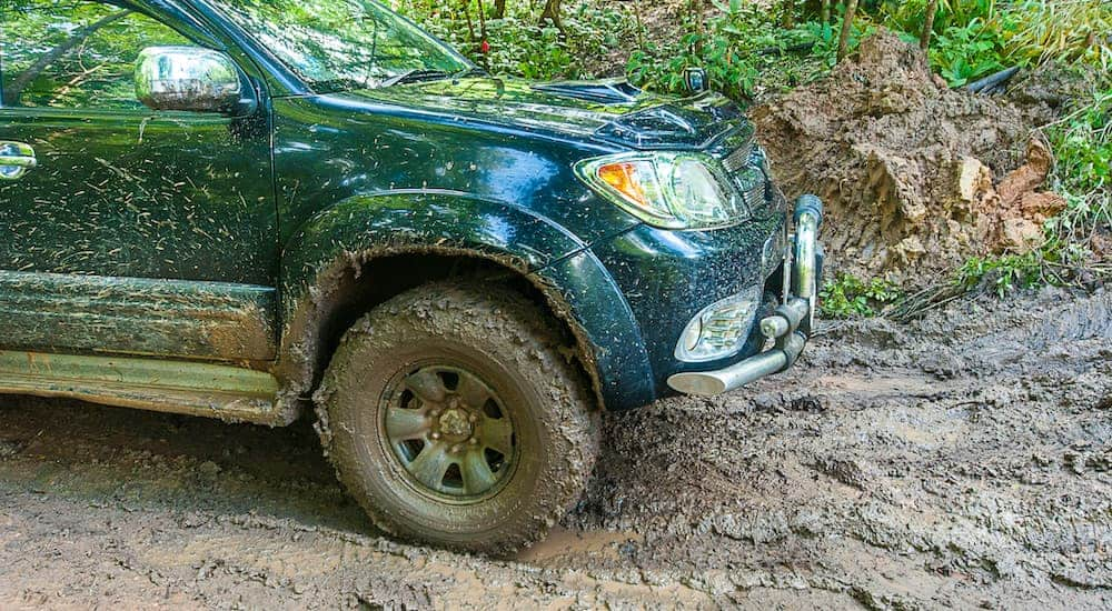 A green truck is shown driving through the mud.