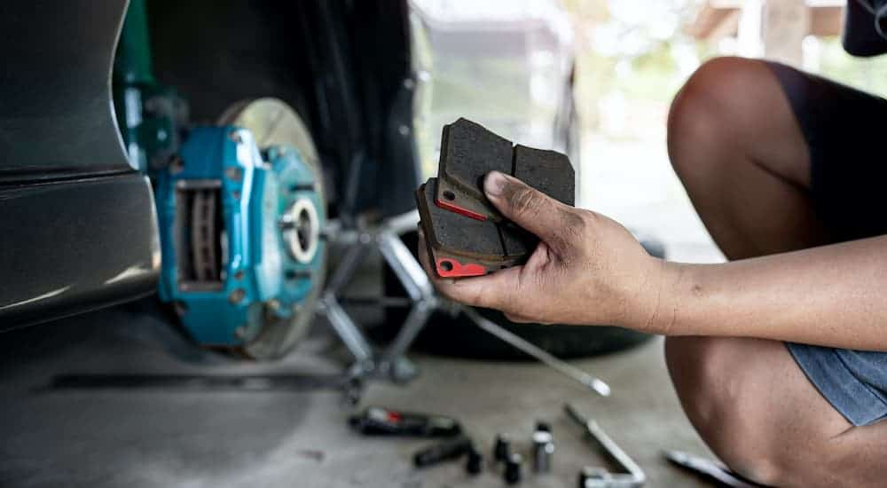 A close up shows a hand holding brake pads during a brake service.