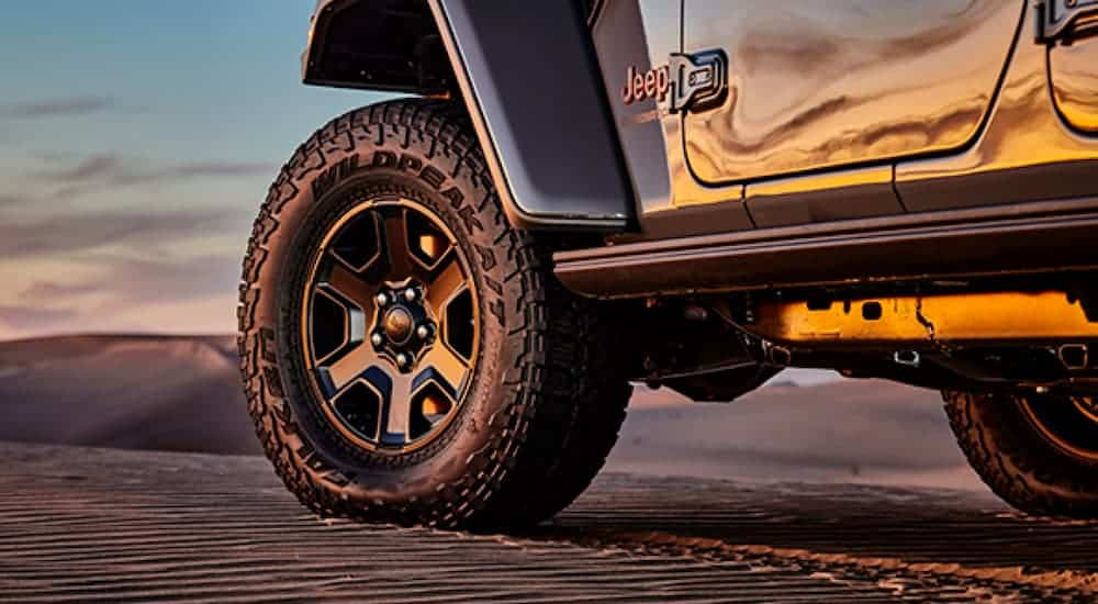 A Falken Wildpeak tire is on a grey 2020 Jeep Gladiator at sunset.