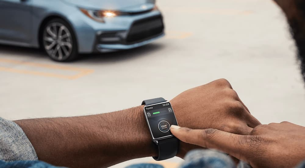 A person is using their smart watch to start the 2022 Toyota Corolla XSE.